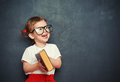 Happy  girl schoolgirl with book from blackboard Royalty Free Stock Photo