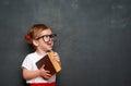 Happy girl schoolgirl with book from blackboard Royalty Free Stock Photo