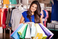 Happy girl on a shopping spree cute young woman doing some serious and smiling Stock Photos