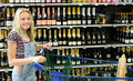 Happy girl with shopping trolley bottles of alcohol on supermarket shelves in background Royalty Free Stock Images