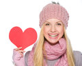 Happy girl showing heart shaped postcard portrait of in winter clothes Stock Image