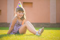 Happy girl sitting on green gras at birthday party pretty grass in hat Stock Images