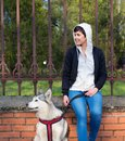 Happy girl sitting with her pet husky dog in the park Royalty Free Stock Photo