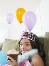 Happy girl on sofa with balloons and cupcake closeup portrait of a young sitting Stock Images