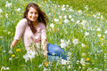 Happy girl in spring sitting on flower field Stock Photos