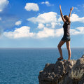 Happy girl standing on a cliff side young woman with arms raised against blue sky with clouds Royalty Free Stock Image