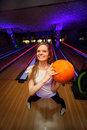 Happy girl stands and keeps ball in bowling club Royalty Free Stock Photo