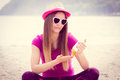 Happy girl in straw hat and sunglasses using sun lotion, sun protection on beach Royalty Free Stock Photo