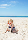 Happy girl in striped swimsuit playing with sand on white beach Royalty Free Stock Photo