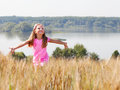 Happy girl in summer field near lake on a sunny day Royalty Free Stock Photo