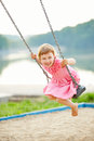 Happy girl swinging on swing in summer a playground Royalty Free Stock Photos