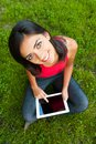 Happy girl with tablet on the grass Stock Photos