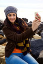 Happy girl taking picture of herself in winter young woman playing with cell phone Stock Image