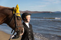 Happy girl teenager with his horse looking at the sea autumn Stock Images