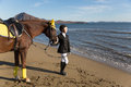 Happy girl teenager with his horse looking at the sea autumn Stock Photography