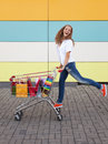 The happy girl the teenager joyfully jumps near to the cart full of purchases Stock Photography