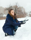 Happy girl throwing up snowflakes in wintry park Stock Photos