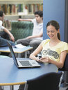 Happy girl using cellphone in library teenage with laptop on table Royalty Free Stock Photos