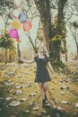 Happy girl walking alone with ballons and smiling Royalty Free Stock Photo
