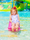 Happy girl on water attractions smiling cheerful baby enjoying warm sunny day swimming in poolside carefree childhood summer Royalty Free Stock Image