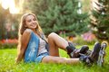 Happy girl wearing roller skates sitting grass park Stock Photo