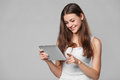 Happy girl in white shirt using tablet. Smiling woman with tablet pc, isolated on grey background Royalty Free Stock Photo