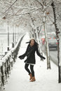 Happy girl in winter season twists fresh snow near the holidays Royalty Free Stock Photo