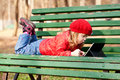 Happy girl working with tablet pc little wearing a red and lying on bench in the park Royalty Free Stock Images