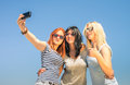 Happy girlfriends taking selfie against blue sky friendship summer concept with new trends and technology best friends enjoying Royalty Free Stock Photo
