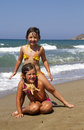 Happy girls on the beach with starfish Stock Photos