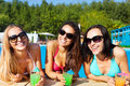 Happy girls with beverages on summer party in the pool Royalty Free Stock Images