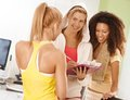 Happy girls at the gym talking with personal trainer Stock Photography
