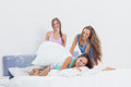 Happy girls having fun at slumber party in bed home bedroom Stock Image