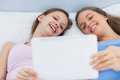 Happy girls lying in bed holding tablet and smiling at sleepover Royalty Free Stock Photos