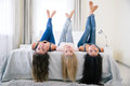 Happy girls lying on the bed wth raised legs portrait of a three and looking at camera at home Stock Images