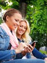 Happy girls outdoors two beautiful smiling young girl in jeans jackets with cell phone sitting on a bench in a park Stock Image