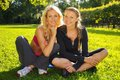 Happy girls outdoors two smiling athletic sitting on a grass in a park Stock Images