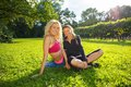 Happy girls outdoors two smiling athletic sitting on a grass in a park Royalty Free Stock Image