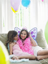 Happy girls sitting on sofa in party costumes portrait of two young Royalty Free Stock Image