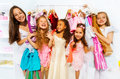 Happy girls during standing among clothes hangers Royalty Free Stock Photo