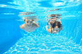 Happy girls swim underwater in pool two and having fun children on summer vacation kids sport concept Royalty Free Stock Photos