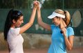Happy girls on tennis court Stock Images