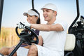 Happy golf couple driving cart Royalty Free Stock Images