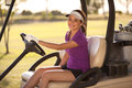 Happy golfer driving a golf cart Royalty Free Stock Photo
