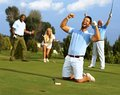 Happy golfer in flush of victory kneeling at hole with raised fists after putting golf ball to the hole Stock Photos