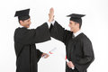 Happy grads two cheerful men in mortarboards clapping the hands Stock Images