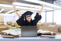Happy graduate laughing in class female grad raised her arms classroom with books and laptop Royalty Free Stock Photo