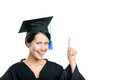 Happy graduating student in black academic gown and cap making the attention gesture isolated on white background Stock Photos