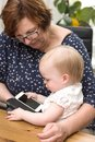 Happy grandmother and cute granddaughter using smartphone, teaching