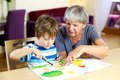 Happy grandmother doing homework with grandson Royalty Free Stock Images